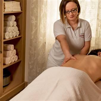 Mann erhält Rückenmassage von einer Therapeutin
