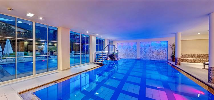 Blue illuminated indoor hotel pool at night
