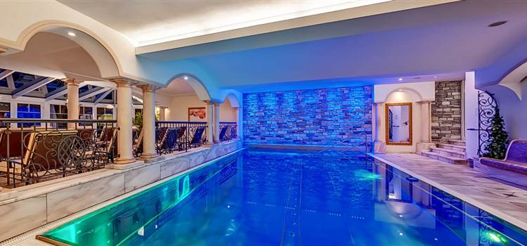 Blue illuminated indoor hotel pool at night