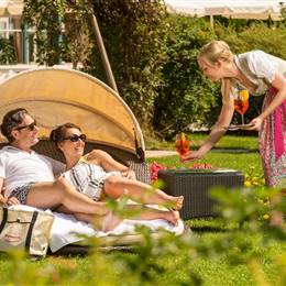 Pair lies on relax furniture on sunbathing lawn and gets drinks served