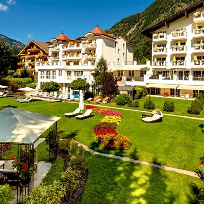 Hotel mit großer Liegewiese und Außenpool im Sommer