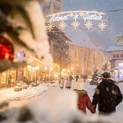 Personen in verschneitem Ort bei Adventstimmung