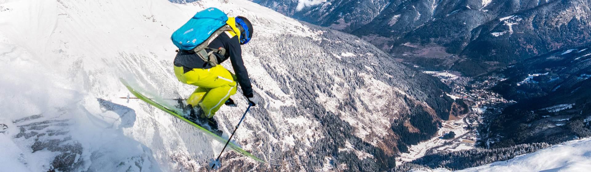Skifahrer springt mit Blick ins Tal