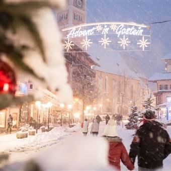 Paar geht durch Winterort bei Schneefall