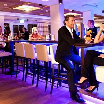 Paar in Abendkleidung sitzt an Hotelbar