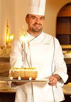 Chef with chef's hat holds birthday cake in his hand