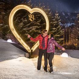 Couple stands in front of illuminated heart in winter landscape