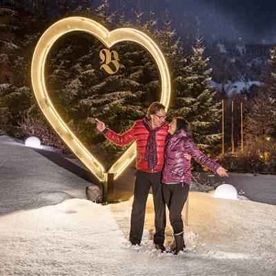 Paar steht vor beleuchtetem Herz in Winterlandschaft