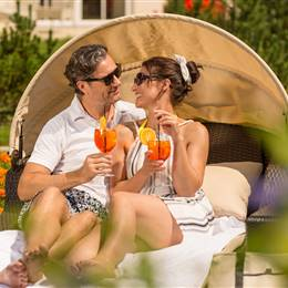 Pair sits on a relax couch drinking Aperol Sprizz