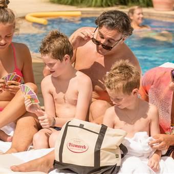 Familie sitzt bei einem Hotelpool und spielt Karten