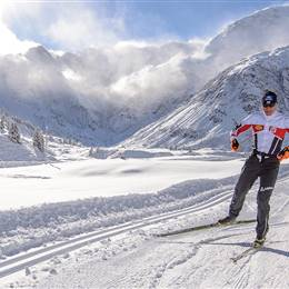 Cross-country skier between mountain landscapes in winter