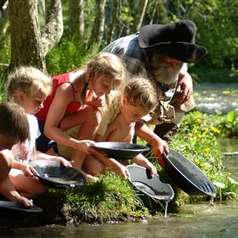 Kinder beim Goldwaschen im Wald bei einem Fluss