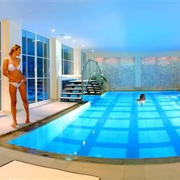 Illuminated hotel indoor pool with bathing guests