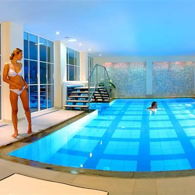Beleuchteter Hotel-Indoor Pool mit Badegästen