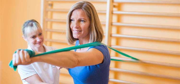 Frau hält Stretching-Band bei einer Sprossenwand