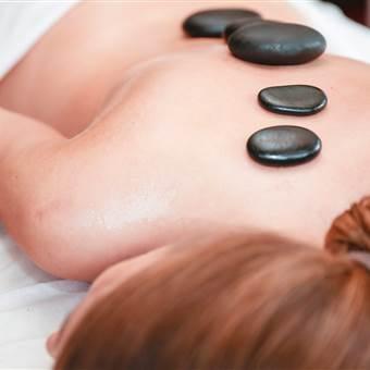 Frau liegt auf dem Rücken auf einer Massagebank mit Hot Stones