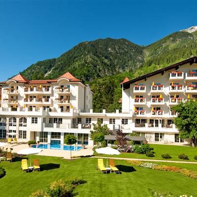 Panoramaansicht eines Hotels mit Liegewiese im Sommer