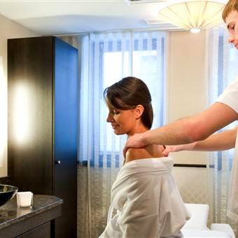 Frau erhält Schultermassage von einem Therapeuten