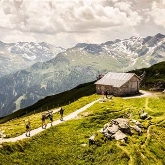 Wanderer auf dem Weg zur Berghütte in den Bergen im Sommer