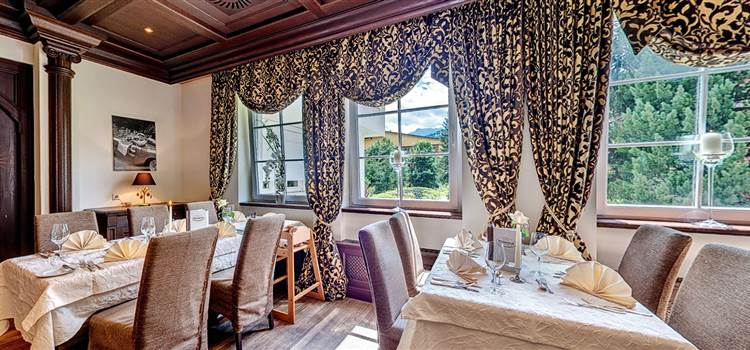 Restaurantbereich mit gedeckten Tischen und schwarz gelben Vorhängen