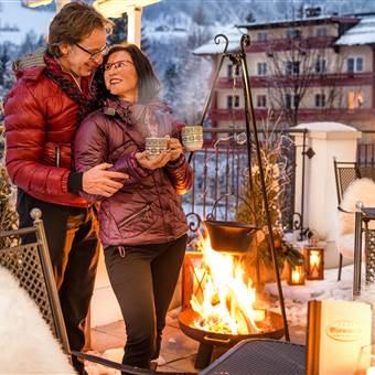Paar steht an Feuerstelle auf Terrasse und trinkt Tee