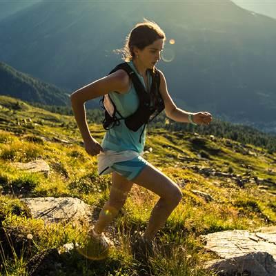 Frau läuft auf einen Berg im Sommer