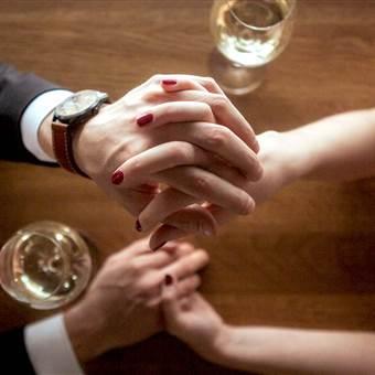 Paar hält Hände am Tisch mit Weingläsern