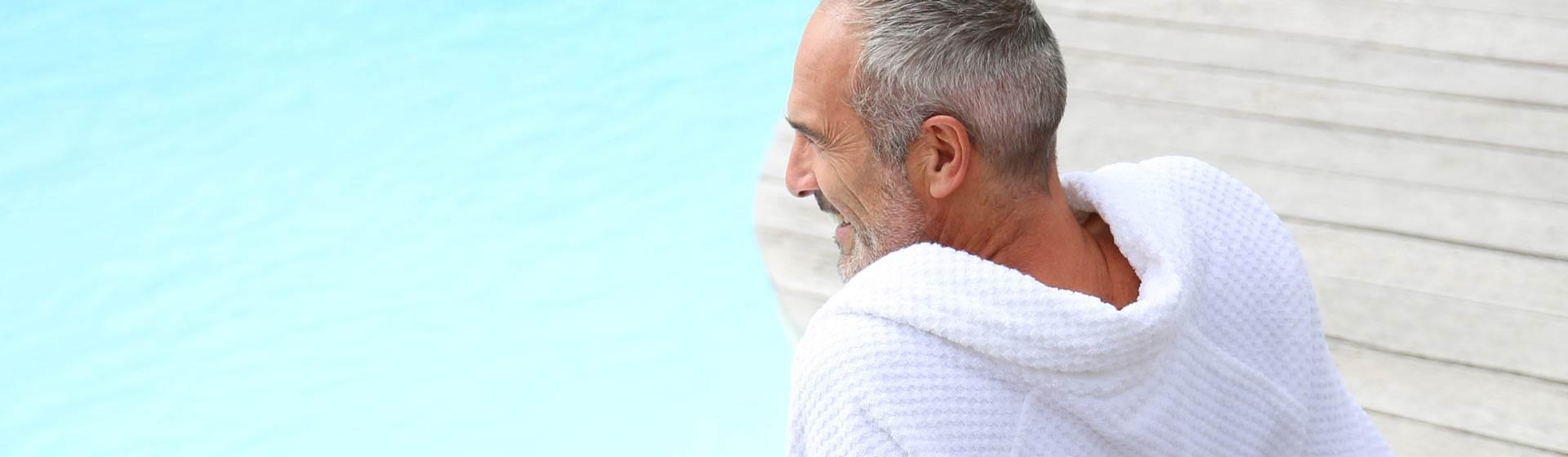 Mann sitzt im Bademantel am Beckenrand