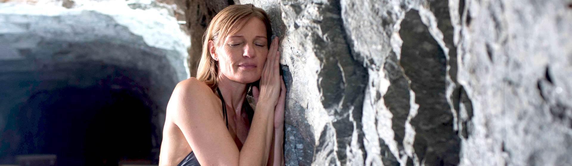 Frau lehnt an einer Höhlenwand mit geschlossenen Augen