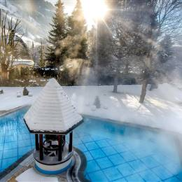 Heated outdoor pool surrounded by snow
