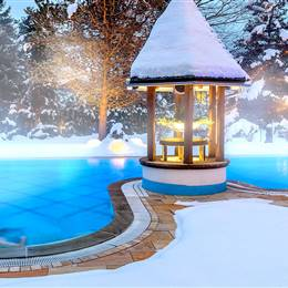 Outdoor pool surrounded by snow in winter