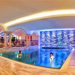 Couple swims in a hotel indoor pool at night