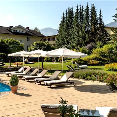 Hotel mit Außenpool und Relaxliegen mit Sonnenschirmen