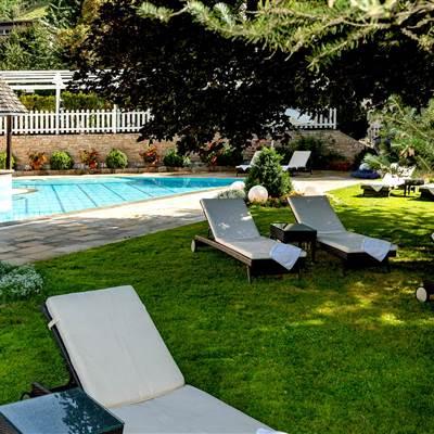 Hotelaußenbereich mit Grünanlage, Pool und Relaxliegen