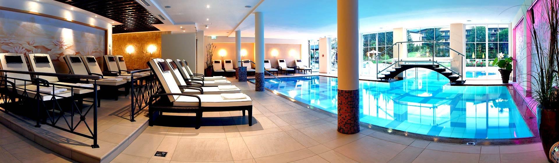 Indoorpool mit Relaxliegen und Zugang zu Außenpool