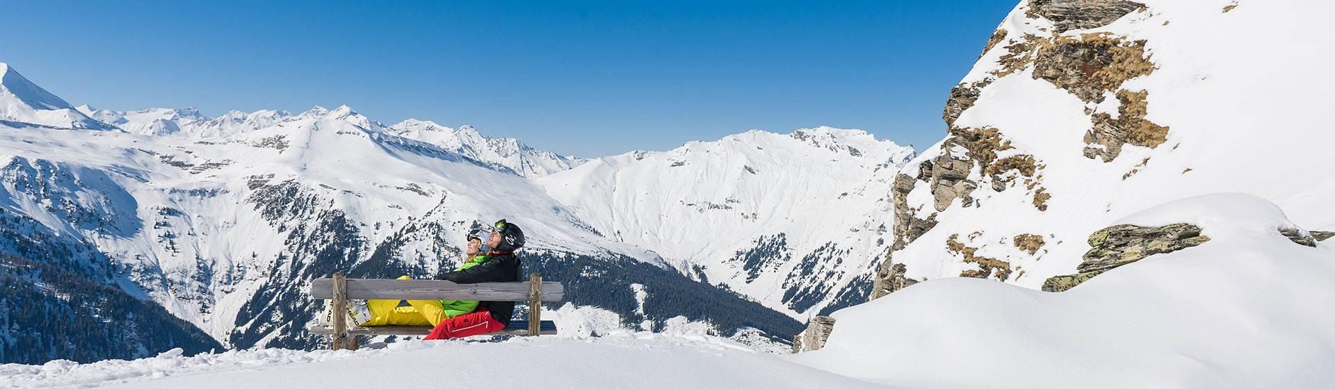 Paar relaxt im Winter auf einer Bank in den Bergen