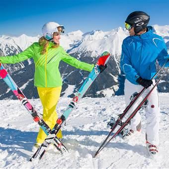 Paar steht mit Skiausrüstung auf einer Abfahrt