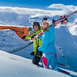 Couple in ski clothes and with ski equipment in the mountains