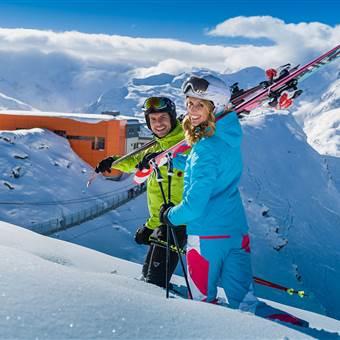 Paar in Skikleidung und mit Skiausrüstung in den Bergen