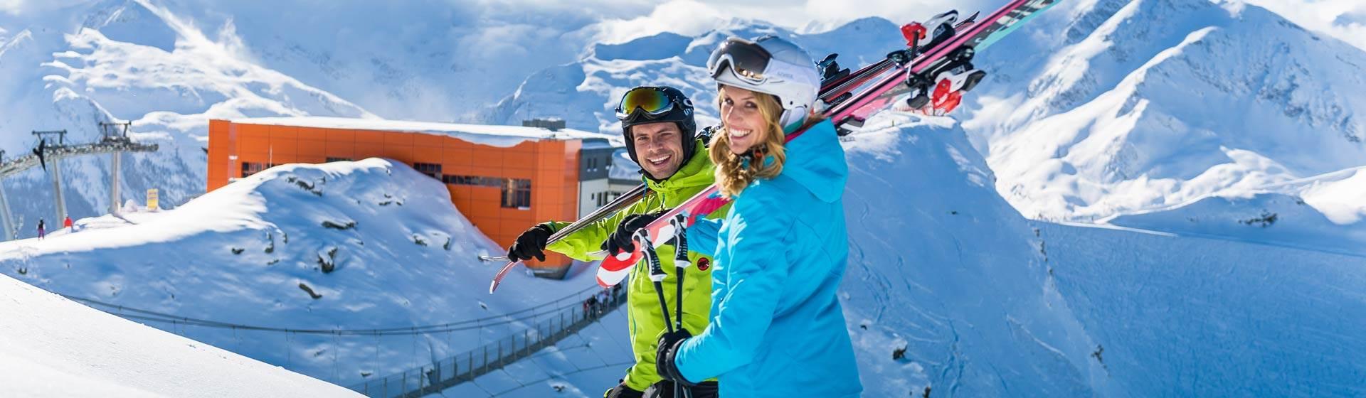 Paar steht auf Skipiste und schultert Skier