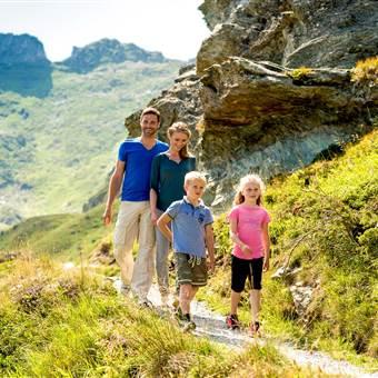 Familie wandert im Sommer in den Bergen