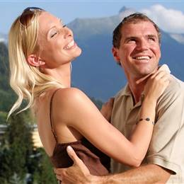 Couple hugging in front of mountain scenery in summer