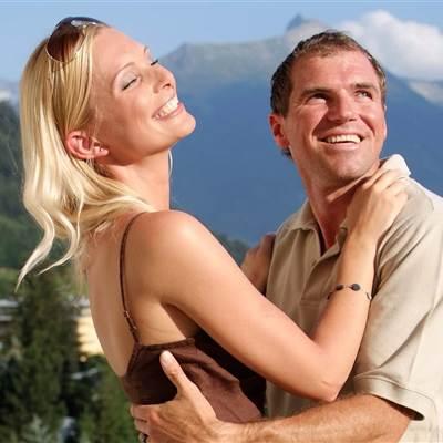 Paar umarmt sich vor Bergkulisse im Sommer