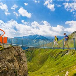 Couple walks over suspension bridge in the mountains