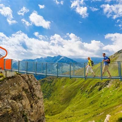 Paar spaziert über Hängebrücke in den Bergen