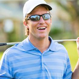 Golfer with sunglasses holds golf clubs behind his shoulders