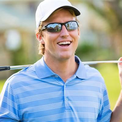 Golfer mit Sonnenbrille hält Golfschläger hinter den Schultern