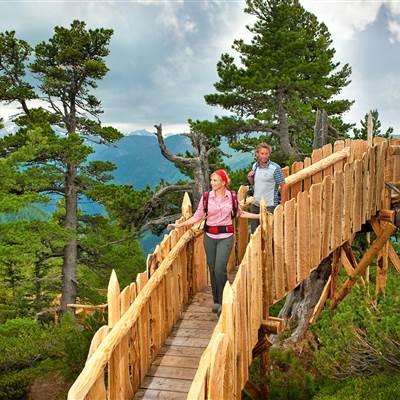 Paar geht über Holzbrücke in den Bergen