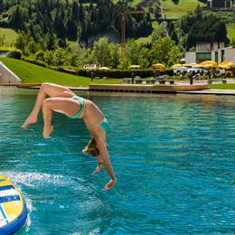 Girl jumps from a SUP into a swimming lake