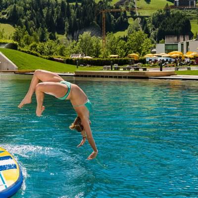 Mädchen springt von einem SUP auf einem Badesee